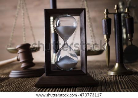 Law theme, hourglass, golden scales of justice, gavel and books on brown background
