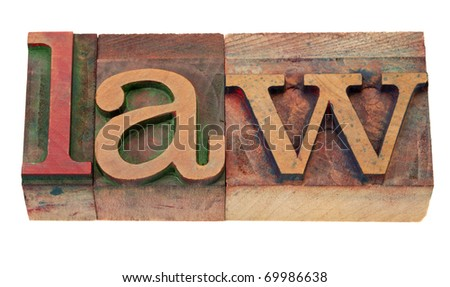law - word in vintage wooden letterpress printing blocks, stained by color inks, isolated on white - stock photo