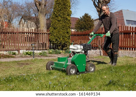 Lawn Aerator.A lawn aerator is a garden tool or machine designed to aerate the soil in which lawn grasses grow - stock photo