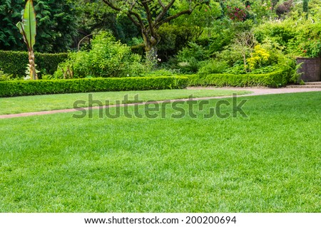 Lawn and pathway in a large garden - stock photo