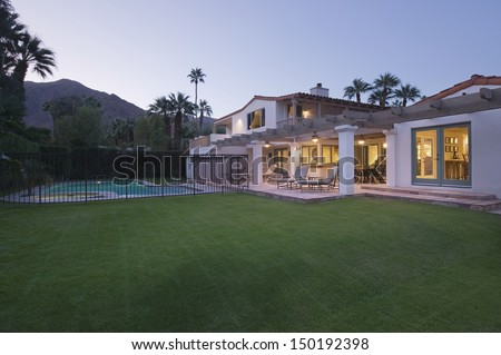 Lawn and swimming pool with lit exterior of home against the sky - stock photo