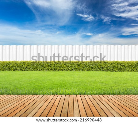 Lawn and wooden floor with hedge and White fence  on blue sky background .  - stock photo