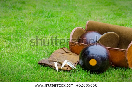 Lawn Bowls. Two wooden bowling balls on freshly cut grass with measuring device, leather bag and cloth. Landscape with copy space.