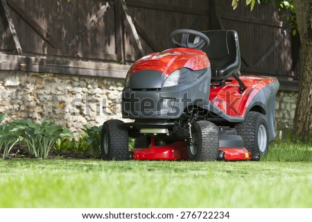 Lawn mower at the garden - stock photo