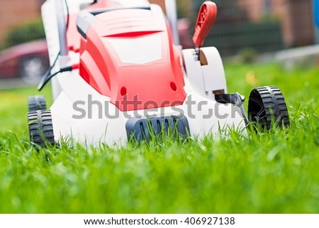 Lawn mower cutting green grass. Work in the garden. Spring gardening