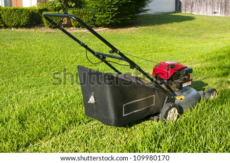 Lawn mower cutting pathway in grass - stock photo
