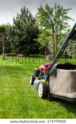 Lawn mower in garden - stock photo