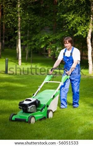 lawn mower man working on the backyard - stock photo