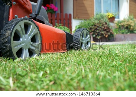 Lawn mower on a lawn in the garden / gardening - stock photo