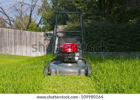 Lawn mower on cut grass path in yard - stock photo