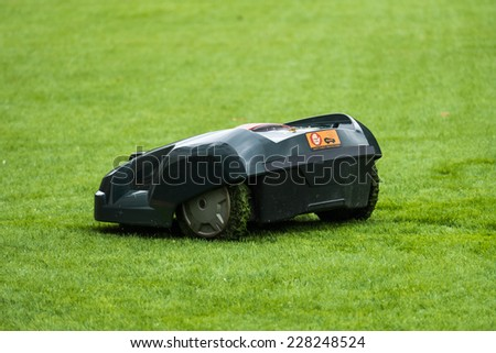 Lawn mower robot in grass, side view - stock photo