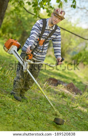 lawn mower worker man cutting grass in green field  - stock photo