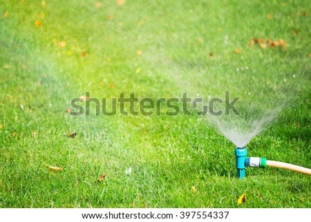 Lawn water sprinkler spaying over green grass. Irrigation system