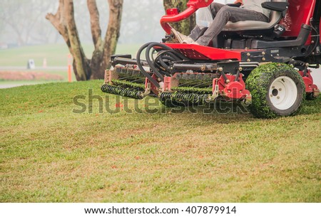 Lawnmower cutting grass , Second cut Lawnmower.Take front mower. - stock photo