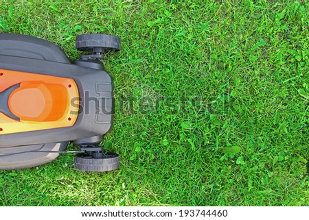 lawnmower on green grass - stock photo