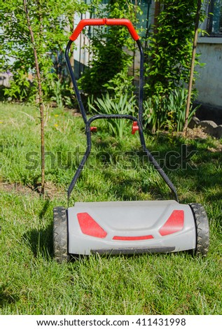 lawnmower on green grass in garden