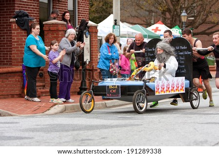 "LAWRENCEVILLE, GA - MARCH 29:  A team pushes the ""bed of Moses"" in the annual Lawrenceville Bed Race, to benefit a local Gwinnett County homeless shelter, on March 29, 2014 in Lawrenceville, GA.  - stock photo"
