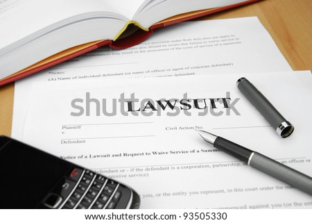 lawsuit form with pen and cell phone - stock photo