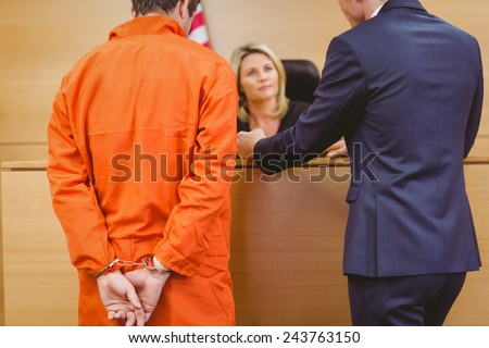 Lawyer and judge speaking next to the criminal in handcuffs in the court room - stock photo