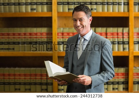 Lawyer holding book in the law library at the university - stock photo
