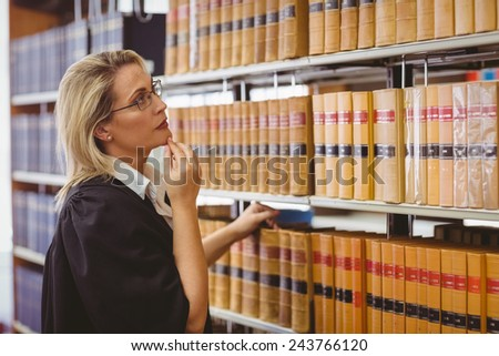 Lawyer wearing glasses and looking for a book in the shelf in library - stock photo