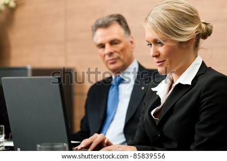 Lawyer with his secretary in his office, he obviously is dictating something - stock photo