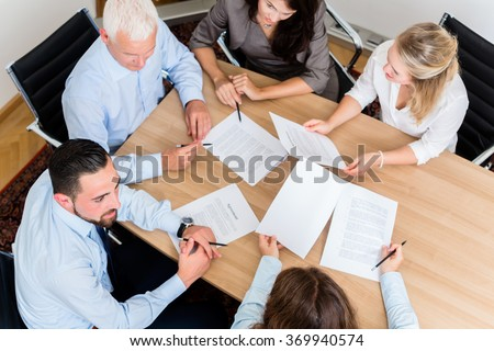 Lawyers having team meeting in law firm reading documents and negotiating agreements - stock photo
