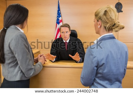 Lawyers speaking with the judge in the court room - stock photo