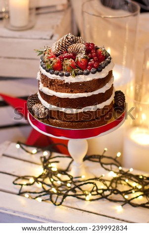 Layer cake decorated with berries on white stand and garland - stock photo