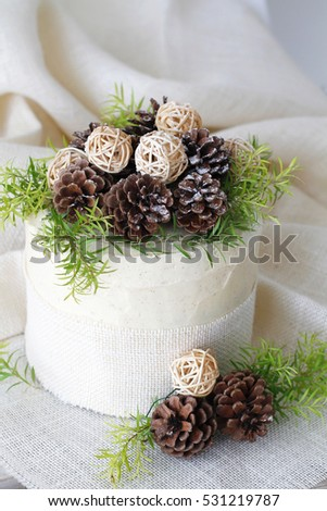 Layer Cake decorated with pine cones and greenery