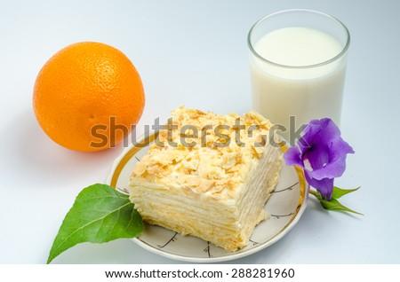 "Layer Cake ""Napoleon"" with cream next to a glass of milk - stock photo"