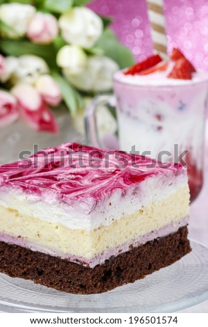 Layer cake with pink icing. Cup of strawberry milkshake decorated with rolled wafer in the background. Party table setting