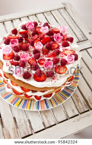 Layered cake decorated with fruit and marzipan flowers viewed from top