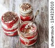 Layered dessert with fruits, nuts and cream cheese in glass jar, selective focus - stock photo