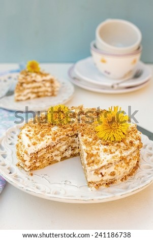 Layered honey cake with chantilly cream and yellow flowers. Selective focus