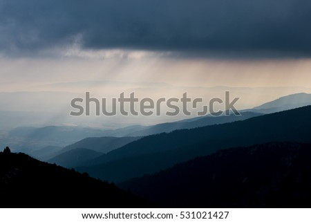 Layered mountain slopes and clouds in blue shades at sunrise
