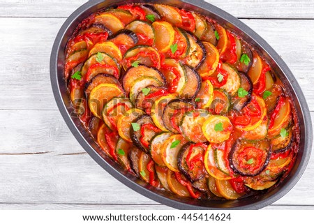 Layered ratatouille in a baking dish:  slices of zucchini, red bell pepper, chili, yellow squash, eggplant, olive oil, parsley and garlic. white background, top view, close-up - stock photo