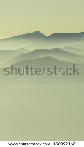 Layers of evening mist over the Apuane Alps, Tuscany, Italy. The Apuan Alps (Italian: Alpi Apuane) are a mountain range in northern Tuscany, Italy, part of the Apennine Mountains. / Mountain mist - stock photo