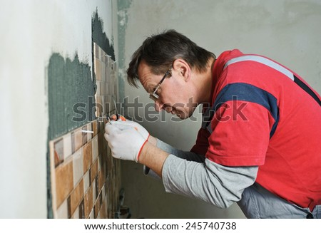 Laying Ceramic Tiles.Tiler aligns seam between the tiles - stock photo