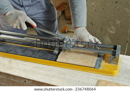 Laying Ceramic Tiles. Tiler cuts tile  manual cutter - stock photo