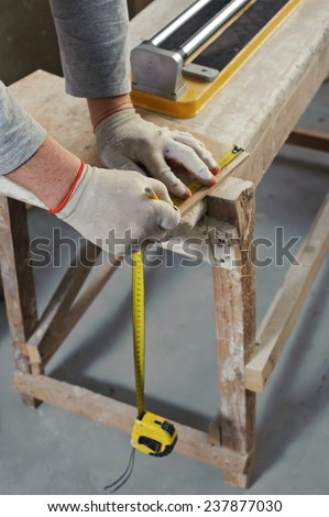 Laying Ceramic Tiles. Tiler measures the tile cutting - stock photo