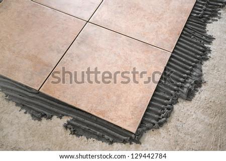laying floor tiles - stock photo