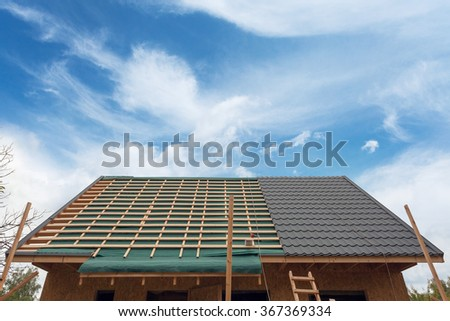 Laying metal tile on the roof. House under construction with screwdriver and roofing iron - stock photo