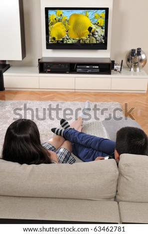 Laying on sofa and watching TV - a series of WATCHING TV images. - stock photo