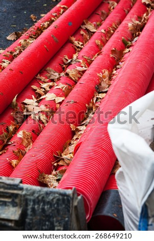 laying red water pipe in the city - stock photo