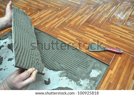 Laying tiles on the floor - stock photo