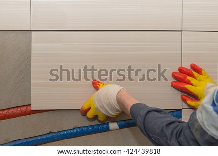 laying tiles on the wall - stock photo