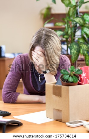 Layoff at work, woman employee upset with things to take away - stock photo