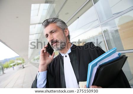 Laywer talking on phone outside courthouse - stock photo