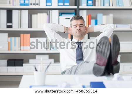 Lazy businessman sleeping in the office with his feet up on the desk and hands behind head